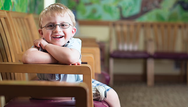 Boy with glasses sitting on a bench